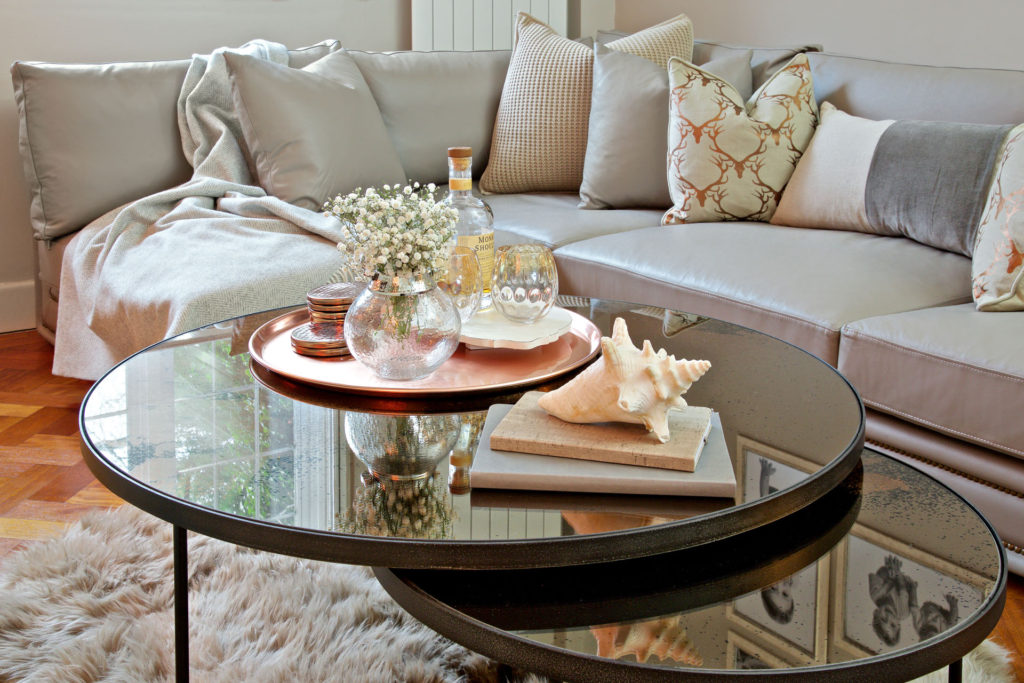 Copper and rose gold styling within this contemporary interior space. The coffee table is bronze, mirrored glass and styled with a range of accessories including a tray and pretty notebooks.