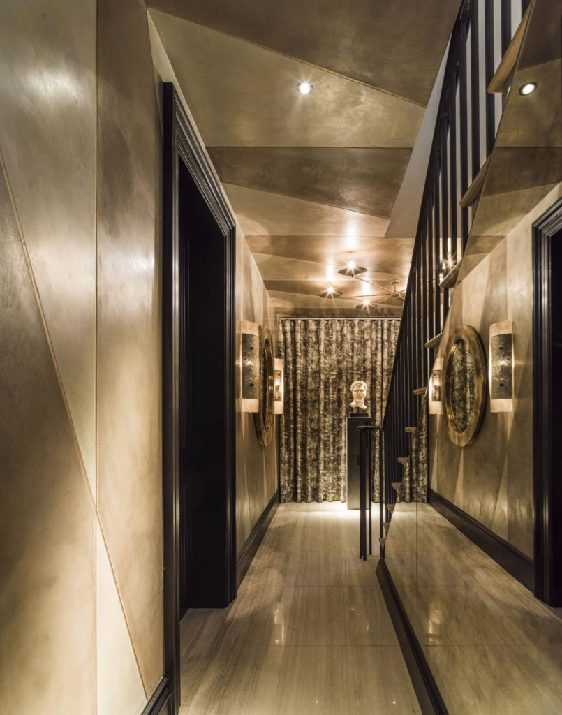 Holiday House London - In the adjoining hallway, Jennifer Kraiem-Ghatan of JKG Interiors had devised a more paired-back, subtle experience through her 'Echoes' scheme. Awash with rich metallic textures and tones - from the brass inlay bespoke plaster panels to the sculptural mirror and lighting - she had devised a calm, sophisticated retreat.